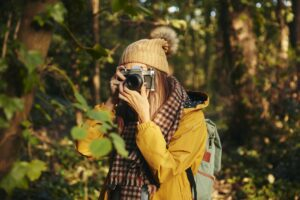 Woman taking photograph with camera in woodland